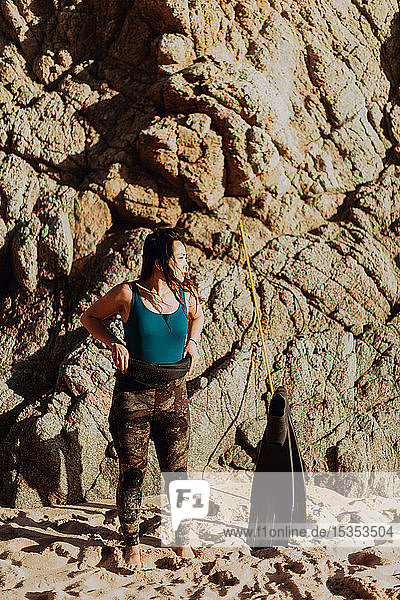 Woman with flippers on beach  rock face in background  Big Sur  California  United States