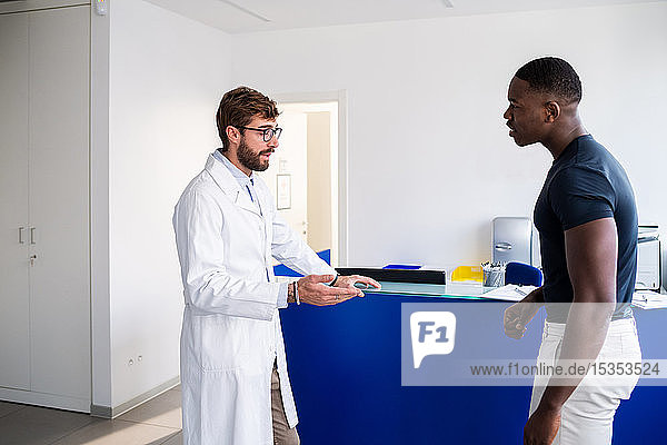Doctor speaking with patient at hospital reception