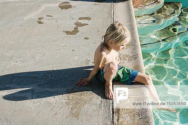 Junge am Schwimmbad sitzend