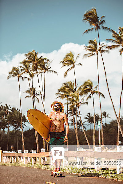 Mid adult male skateboarder wearing straw hat  standing on skateboard carrying surfboard on rural road  portrait  Haiku  Hawaii  USA