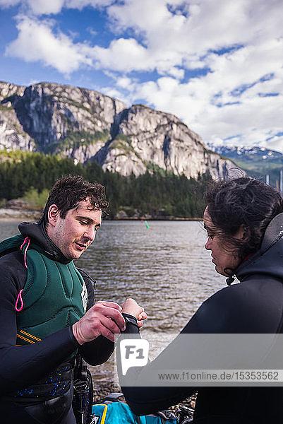 Mann hilft Frau mit Neoprenanzug  Squamish  Kanada