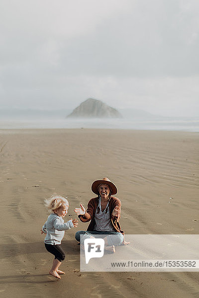 Mother and toddler playing with sand on beach  Morro Bay  California  United States