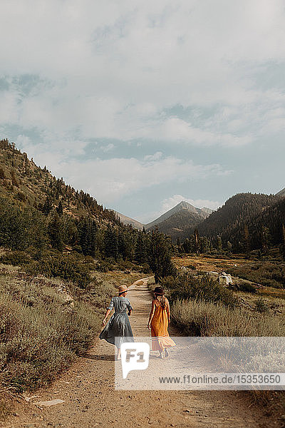 Two woman in maxi dresses strolling on rural valley road  rear view  Mineral King  California  USA