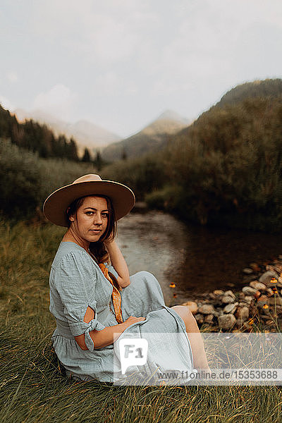 Young woman in stetson sitting by rural river,  portrait,  Mineral King,  California,  USA