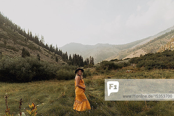 Pregnant mid adult woman in orange maxi dress in rural valley  portrait  Mineral King  California  USA