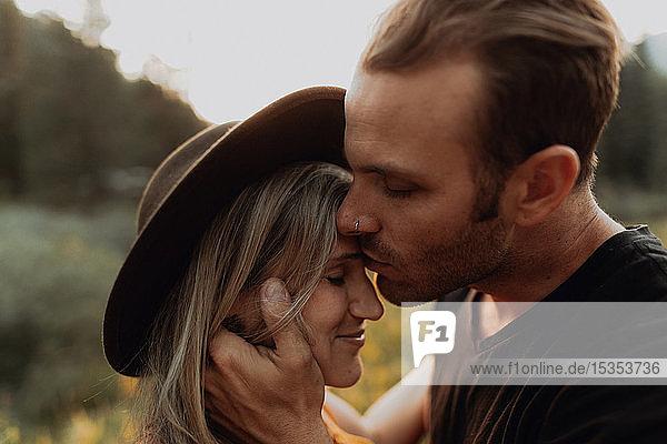 Romantischer mittelgroßer Mann küsst seine Freundin auf die Stirn in einem ländlichen Tal  Porträt  Mineral King  Kalifornien  USA