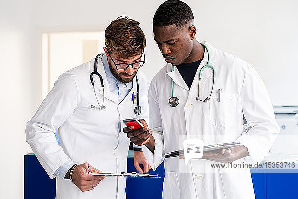 Doctors using smartphone at hospital reception