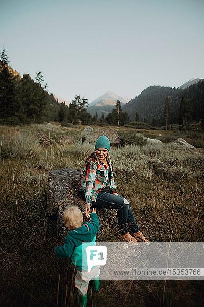 Mutter gibt Kleinkind Tochter helfende Hand zum Sitzen auf Felsbrocken im ländlichen Tal  Mineral King  Kalifornien  USA