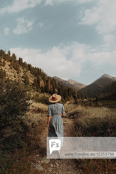 Young woman in stetson and maxi dress strolling on rural valley dirt track  rear view  Mineral King  California  USA