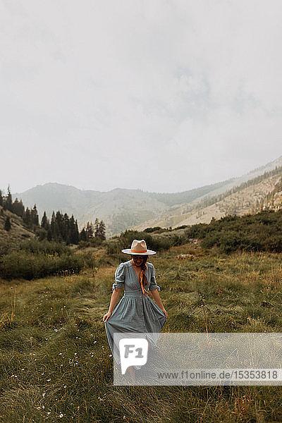 Junge Frau in Stetson hält Maxikleid in ländlichem Tal  Mineral King  Kalifornien  USA