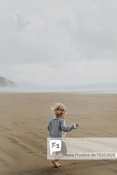 Toddler running on beach  Morro Bay  California  United States