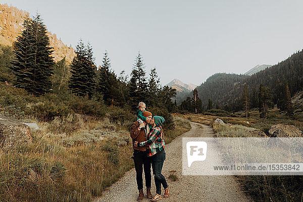 Paar mittlerer Erwachsener mit einer Kleinkind-Tochter  die sich auf der ländlichen Talstraße küsst  Mineral King  Kalifornien  USA