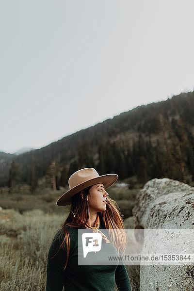 Junge Frau in Stetson schaut über Felsbrocken im ländlichen Tal  Mineral King  Kalifornien  USA