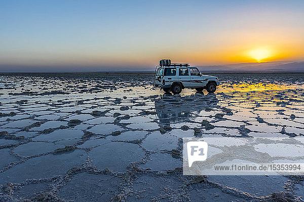 Four-wheel drive vehicle on the salt flats of Lake Karum (Lake Assale) at sunset  Danakil Depression; Afar Region  Ethiopia