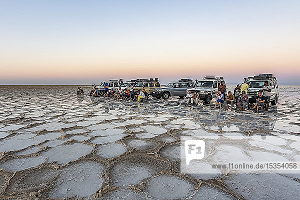 Tourists in front of four-wheel drive vehicle on the salt flats of Lake Karum (Lake Assale) at sunset  Danakil Depression; Afar Region  Ethiopia
