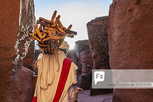 Ethiopian Orthodox priest carrying prayer sticks by Biete Qeddus Mercoreus (House of Saint Mercurius or House of Mark the Evangelist) Ethiopian Orthodox rock-cut church in the Southern Group of the Rock-Hewn Churches; Lalibela  Amhara Region  Ethiopia