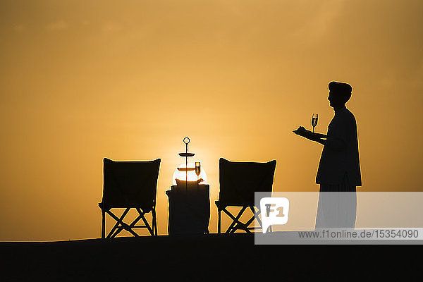 Butler holding champagne glasses after setting up a table for a sundowner drink; Rajasthan  India