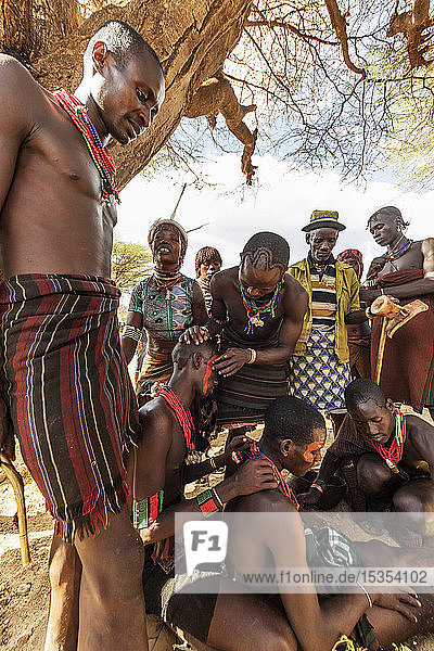 Hamer men getting their faces painted ahead of a bull jumping ceremony  which initiates a boy into manhood  in the village of Asile; Omo Valley  Ethiopia