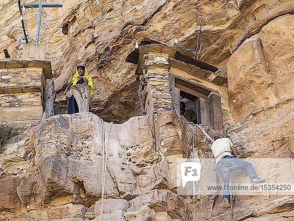 Man climbing on a rope to reach Debre Damo monastery; Tigray Region  Ethiopia