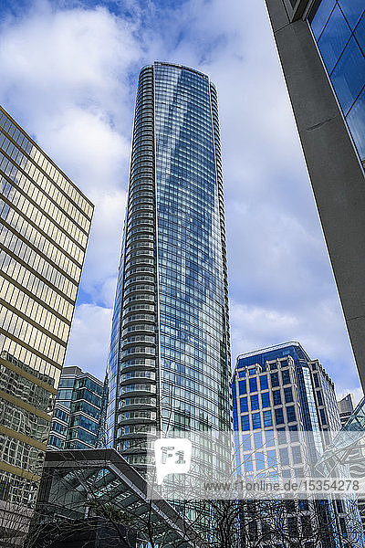 Skyscraper with glass facade reflecting blue sky and clouds; Vancouver  British Columbia  Canada