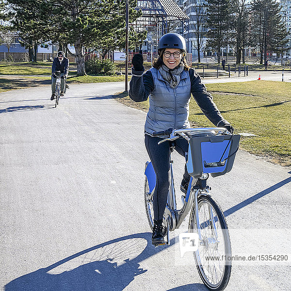 A woman cycling on a paved trail in an urban area; Vancouver  British Columbia  Canada