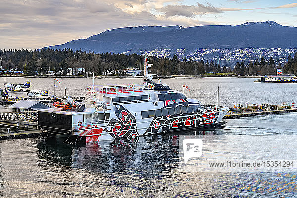 Ferry with indigenous artwork painted on the side  moored at a waterfront; Vancouver  BC  Canada