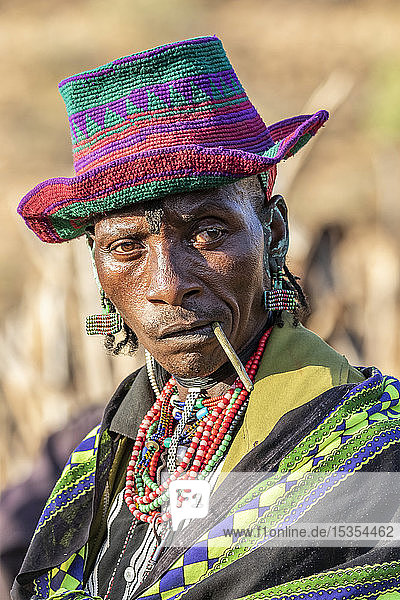Hamer man wearing a colourful hat at a bull jumping ceremony  which initiates a boy into manhood  in the village of Asile  Omo Valley  Ethiopia