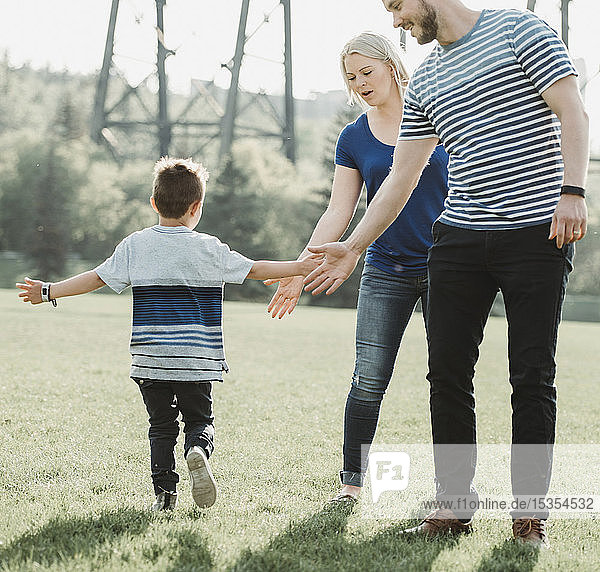 A family with young son playing in a park; Edmonton  Alberta  Canada