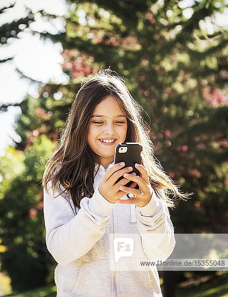 A young girl texting on a smart phone while taking a walk in a city park during a warm and sunny fall day; Edmonton  Alberta  Canada