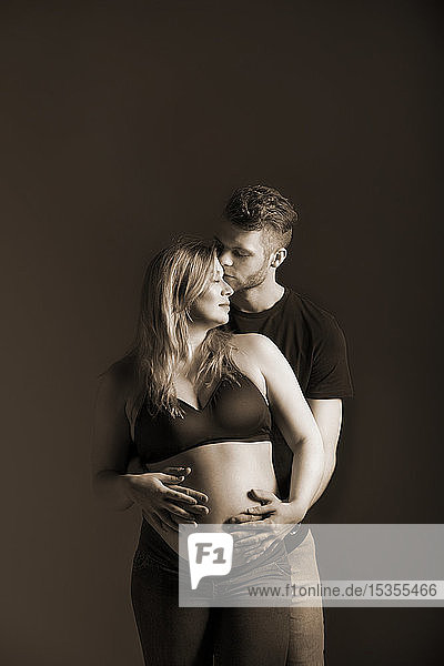 A young expectant couple looking at each other and the father is kissing her forehead and holding her belly in a studio on a dark background; Edmonton  Alberta  Canada