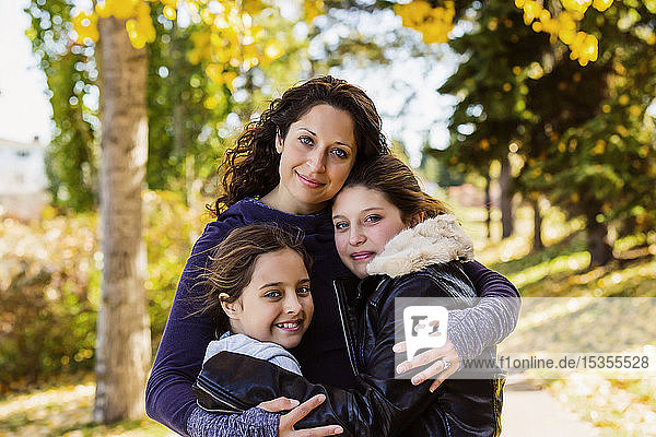 A mother and her two daughters posing for a family portrait in a city park on a warm fall day; Edmonton  Alberta  Canada