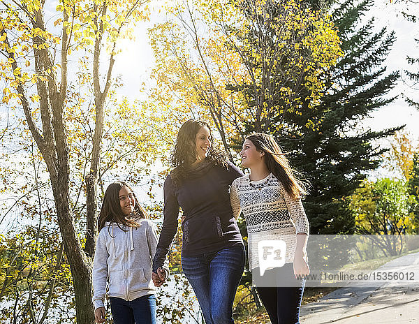 A mother and her two daughters walking and talking on a pathway in a city park on a warm autumn day; Edmonton  Alberta  Canada