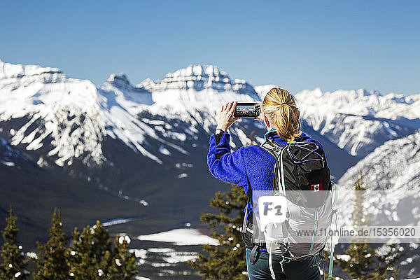 Female hiker on top of mountain with cell phone taking a photo of snow-covered mountain range with blue sky; Banff  Alberta  Canada