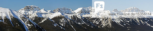 Panorama of snow-covered mountain range and blue sky; Banff  Alberta  Canada