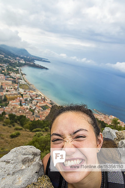 A young female tourist stands on a lookout above the Mediterranean coast; Cefalu  Sicily  Italy