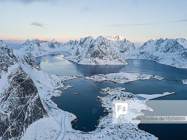 Verschneite Berge am Fjord mit Ort Reine  Sonnenaufgang  Drohnenaufnahme  Lofoten  Norwegen  Europa