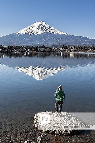 Junge Frau steht auf Stein im Wasser  Kawaguchi-See  hinten Vulkan Mt. Fuji  Präfektur Yamanashi  Japan  Asien