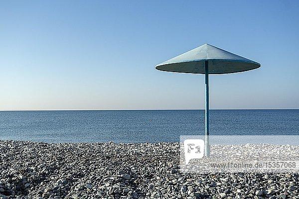 Blue umbrella on the pebble beach  Cyprus  Europe