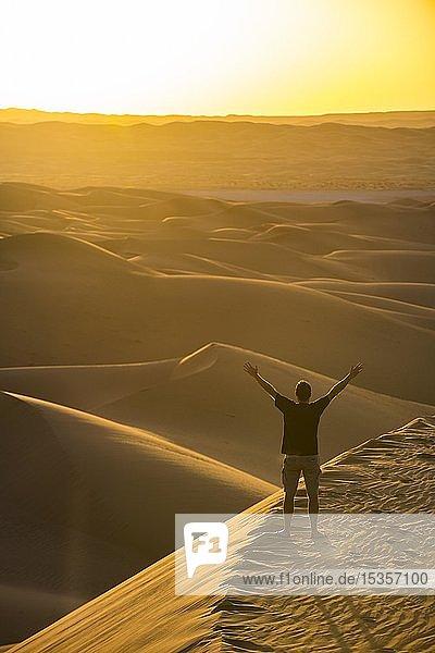 Mensch genießt den Sonnenuntergang in den riesigen Sanddünen der Sahara  Timimoun  Algerien  Afrika