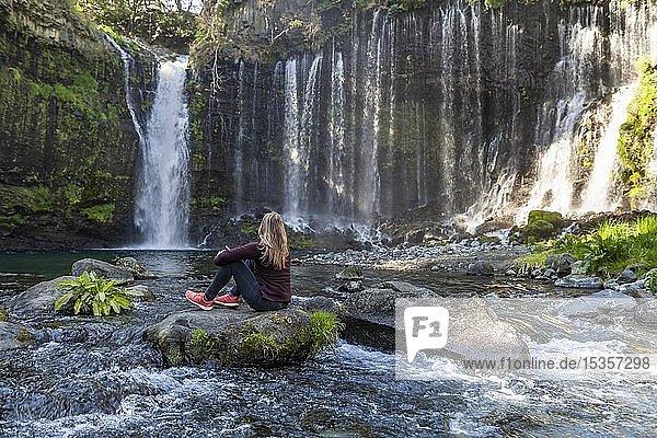 Junge Frau sitzt auf einem Stein in einem Fluss  Shiraito Wasserfall  Präfektur Yamanashi  Japan  Asien