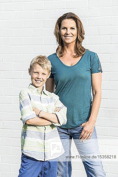 Mutter und Sohn mit verschränkten Armen stehen vor einer weißen Wand  schauen in die Kamera  lächeln  Deutschland  Europa