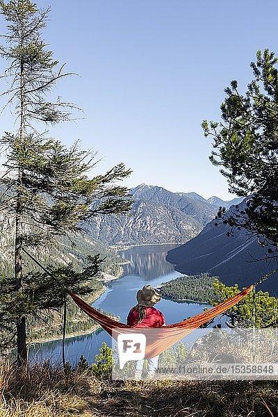 Frau mit Sonnenhut sitzt in einer orangen Hängematte  Panoramablick auf Berge mit See  Plansee  Tirol  Österreich  Europa