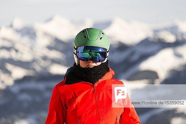 Skifahrerin mit Skihelm und Skibrille blickt in die Kamera  Portrait  hinten Berge  SkiWelt Wilder Kaiser  Brixen im Thale  Tirol  Österreich  Europa