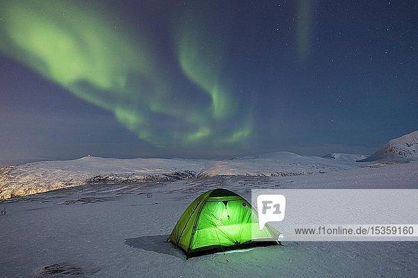 Grün beleuchtetes Zelt im Schnee und Polarlicht über dem Fjellheisen  Tromsö  Norwegen  Europa
