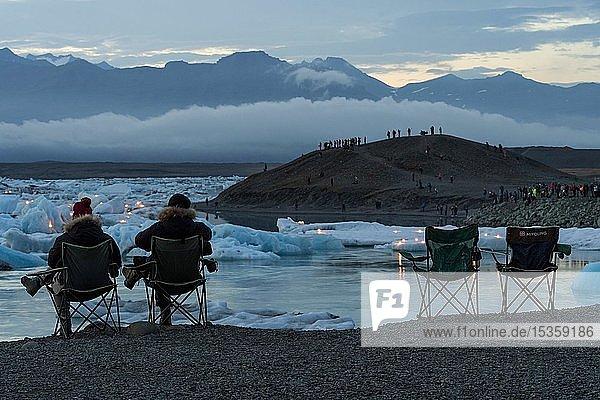 Touristen in Campingstühlen warten auf das Feuerwerk an der Gletscherlagune Jökulsárlón  Massentourismus  Südisland  Island  Europa