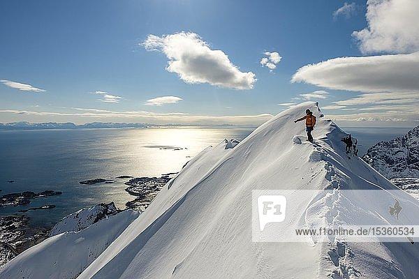 Bergsteiger bei Schnee auf dem Grat des Stortinden,  Svolvaer,  Austvågøy,  Lofoten,  Norwegen,  Europa