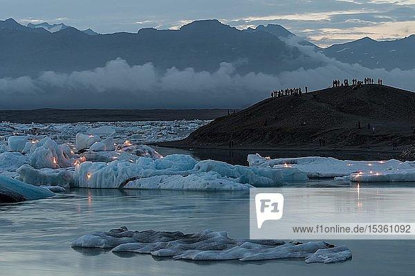 Touristen warten auf das Feuerwerk an der Gletscherlagune Jökulsárlón  Südisland  Island  Europa