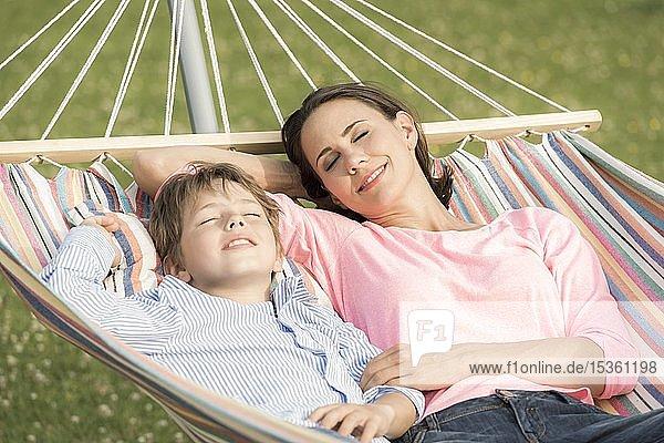 Mutter und Sohn liegen in Hängematte  Augen geschlossen  lächeln  Deutschland  Europa