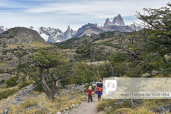 Junge Frau und kleiner Junge wandern vor Gebirgskette mit Berg Monte Fitz Roy bei El Chalten  Nationalpark Los Glaciares  Provinz Santa Cruz  Patagonien  Argentinien  Südamerika