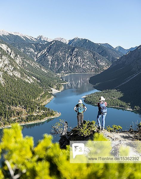 Two hikers look into the distance over the Lake Plansee  surrounded by mountains  Schönjöchl  Plansee  Tyrol  Austria at the back.